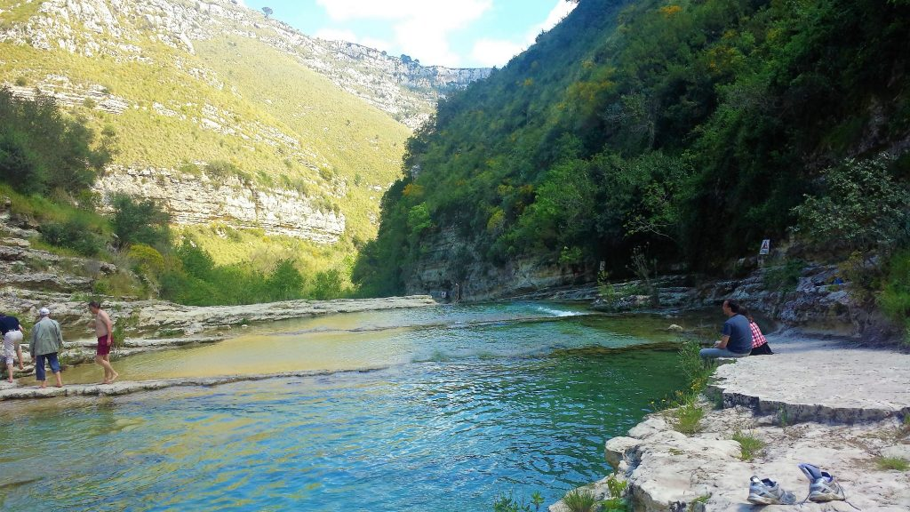 The picture shows the river of Cavagrande natural reserve and some visitors enjoying the beauty of the place.