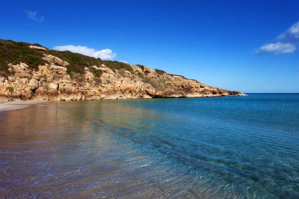 The image shows Calamosche beach in Vendicari natural reserve. The sky is blue and the water is crystal clear. There is also a rocky wall at the end of the beach.
