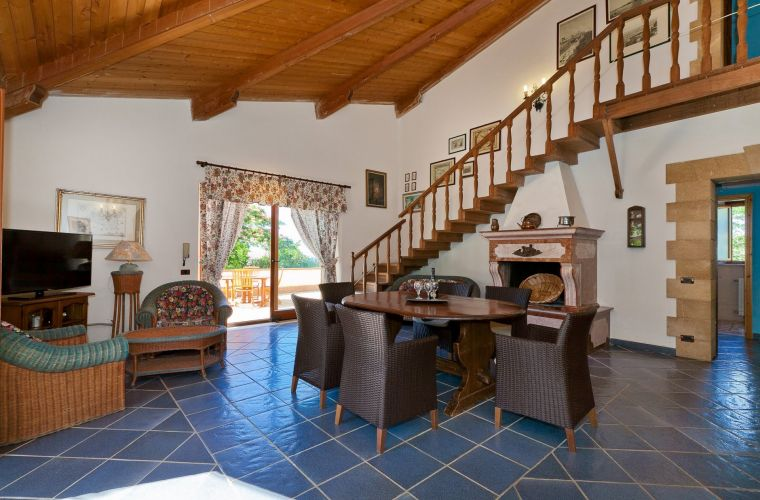 The living room has a cozy fireplace and a wooden staircase leading to the first floor and to the bedroom.