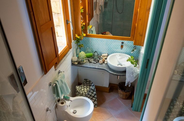 A bathroom with a shower, toilet and bidet.