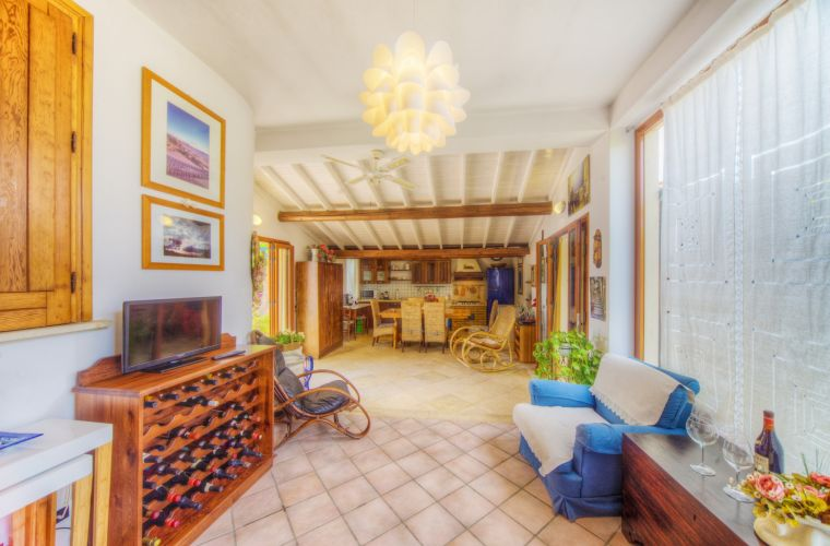 And there is also a sort of winter garden, the very highlight of the house. Spacious and elegant this room has a lounge with the television and a stunning kitchen fully equipped with an elegant wooden table, ideal for your Sicilian summer meals. From this