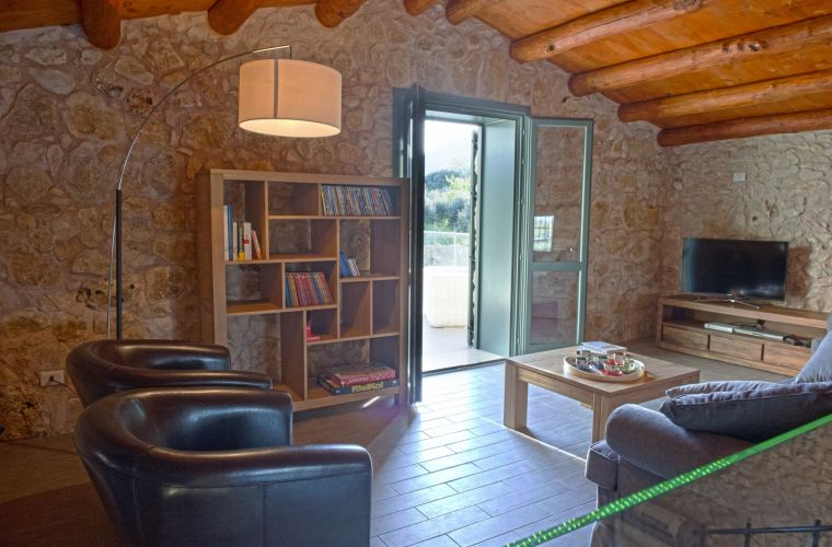 The villa extends over two levels, you enter inside from the large and bright living room, characterized by local stone walls and a staircase leading to the first floor.