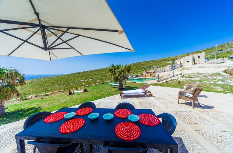 Red table, white stone, green lawn, blue ocean