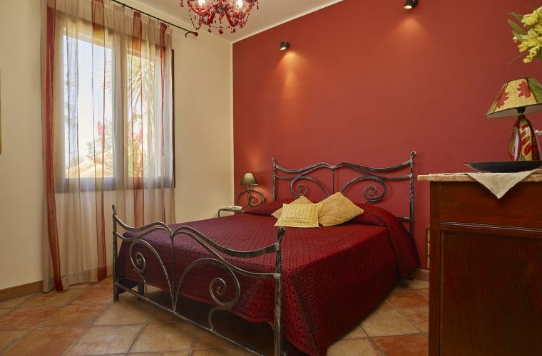 On the ground floor, there is a colorful double bedroom with wrought iron bed. The elegant bathroom is with shower.