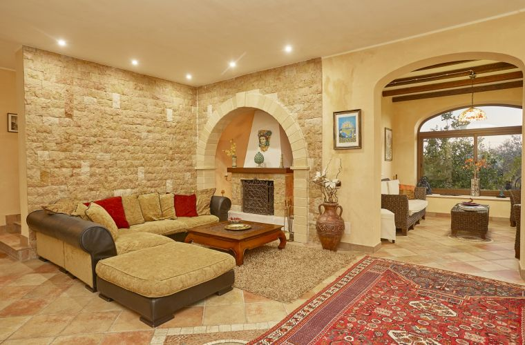The villa has two floors. At the ground floor there is an elegant living room with fireplace. Some of the walls are covered with stones that give a warm atmosphere.