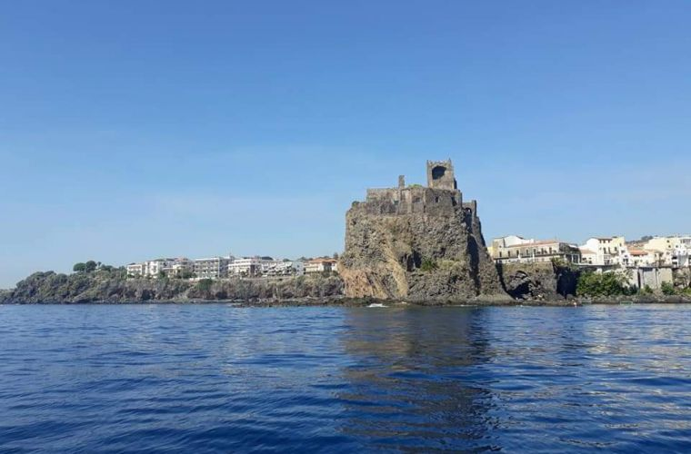 The castle of Acicastello built on the top of a lava rock, along the sailing