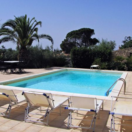 At the back side of the villa there is a pool with showers, sun recliners and gazebo with table and chairs