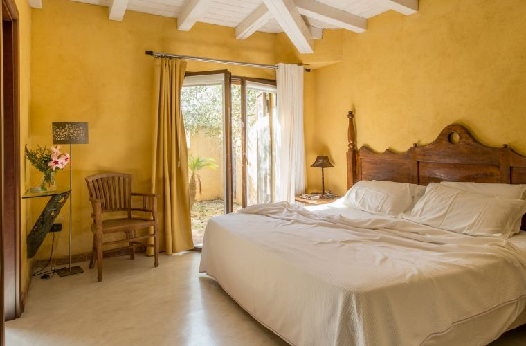 The bedrooms are decorated with warm colors, wooden furniture and balcony doors.